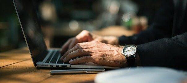 Überstunden: Mann mit Uhr arbeitet am Laptop.